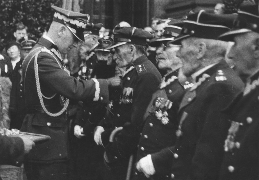 Weterani powstania styczniowego byli traktowani w międzywojennej Polsce traktowani ze szczególną estymą. Maria Mościcka jednak nie zważała na ich sędziwy wiek (domena publiczna).