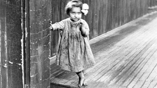 """Fotografia Lewisa H. Hine'a zatytułowana: """"Mała sierota Anne w zakładzie w Pittsburghu"""". Zdjęcie z 1909 roku"""
