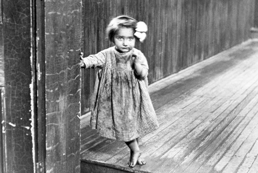 """Fotografia Lewisa H. Hine'a zatytułowana: """"Mała sierota Anne w zakładzie w Pittsburghu"""". Zdjęcie z 1909 roku."""