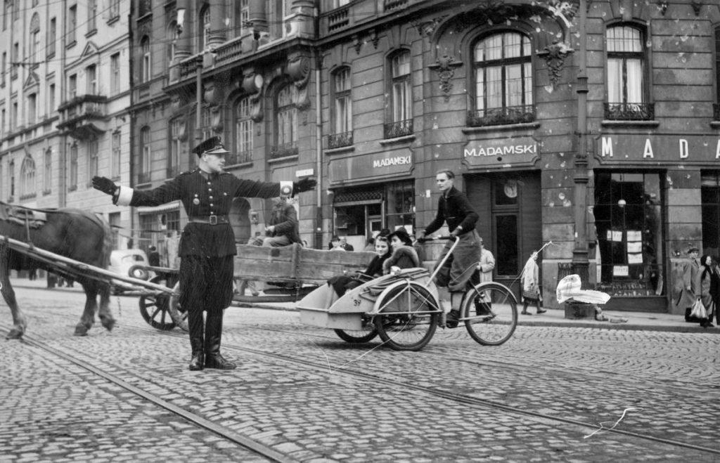 Początkowo zadania Policji Polskiej Generalnego Gubernatorstwa skupiały się na utrzymania porządku publicznego. Na zdjęciu  polski policjant kieruje ruchem na skrzyżowaniu ulic Nowy Świat i Książęcej w Warszawie (domena publiczna).