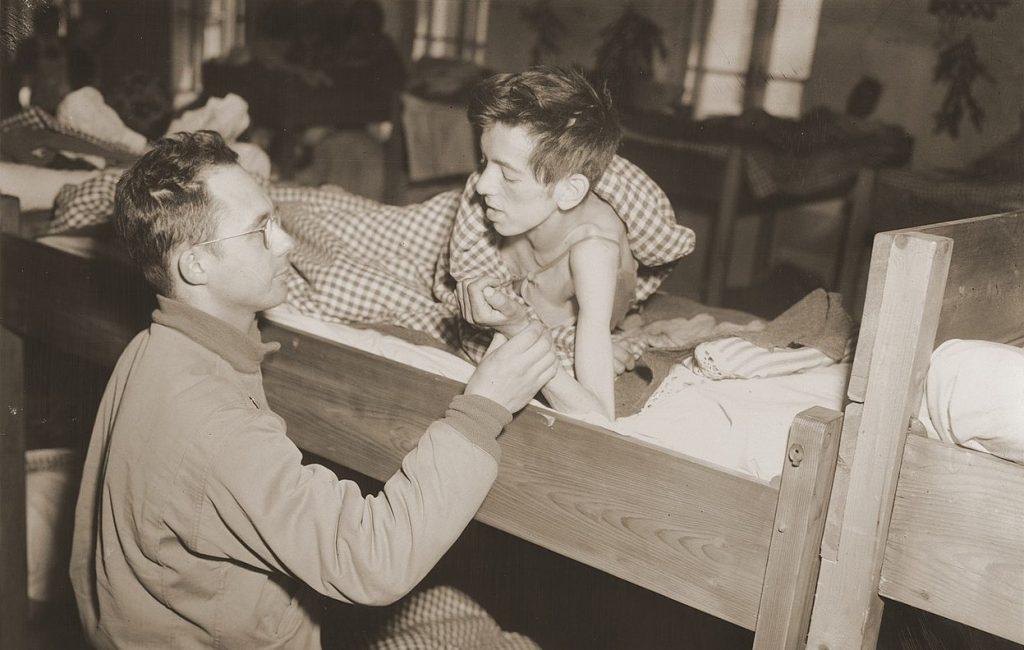 Amerykański lekarz bada jednego z ocalałych więźniów obozu w Flossenbürgu. Zdjęcie wykonane 8 maja 1945 roku (J.P. Musae/domena publiczna).