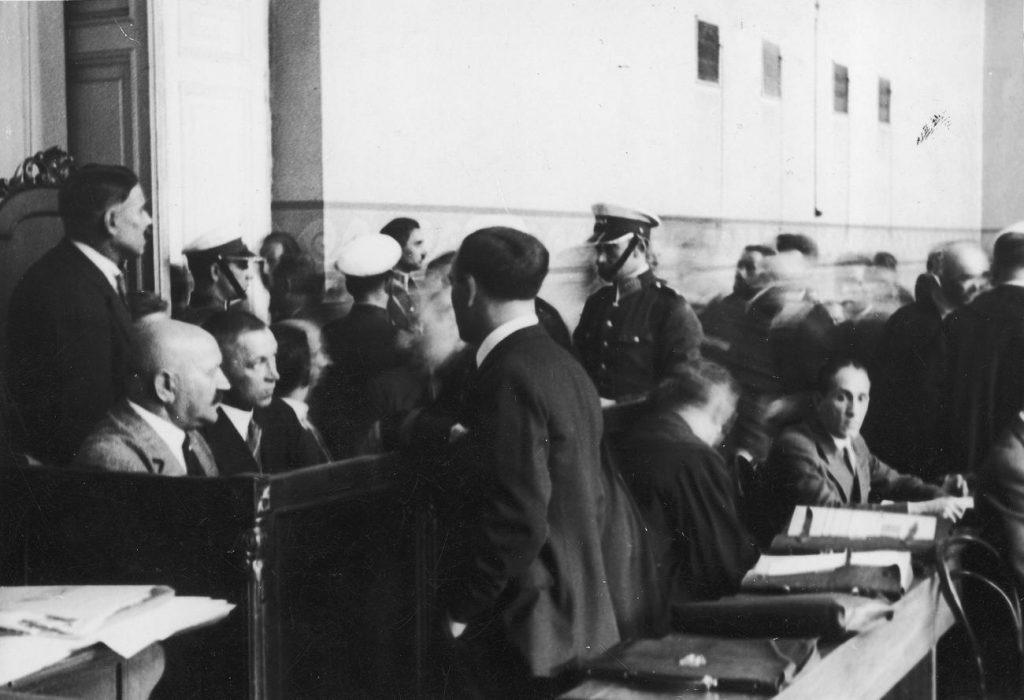 """""""Tata Tasiemka"""" ławie oskarżonych (siedzi pierwszy z lewej) w trakcie procesu z lipca 1932 roku (domena publiczna)."""