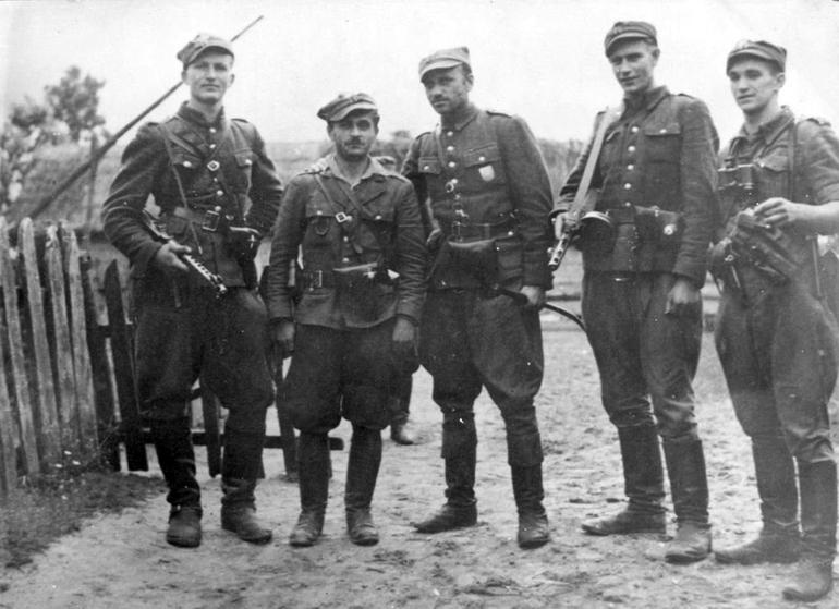 """Po wojnie przez antykomunistyczne podziemie przwinęło się od 120 do 180 tysięcy osób. Na zdjęciu żołnierze 5. Wileńskiej Brygady AK. W środku Zygmunt Szendzielarz """"Łupaszka"""" (domena publiczna)."""