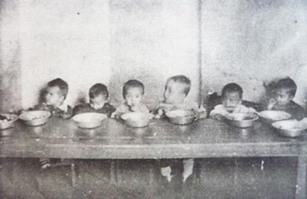 Dzieci z łagrowego sierocińca w trakcie posiłku (domena publiczna).