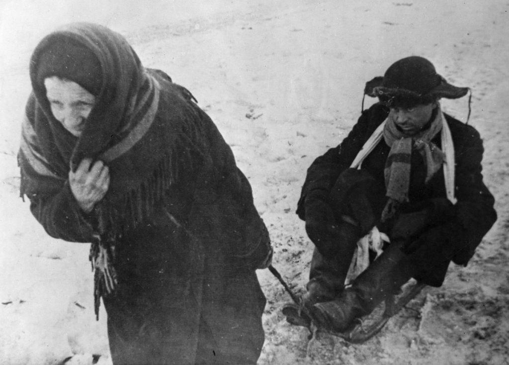Głód sprawiał, że ludzie potrafili posunąć się do wszystkiego, aby tylko zdobyć żywność. Na zdjęciu wyczerpany z głodu mężczyzna ciągnięty na sankach przez starszą kobietę (RIA Novosti archive/Ozjerski/CC-BY-SA 3.0).