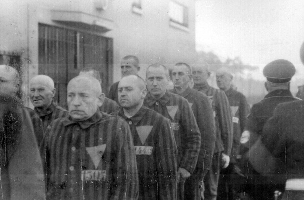 Jedną z grup prześladowanych w nazistowskich Niemczech byli homoseksualiści. Na zdjęciu więźniowie Sachsenhausen, z różowym trójkątem na piersi (Marion Doss/CC BY-SA 2.0).