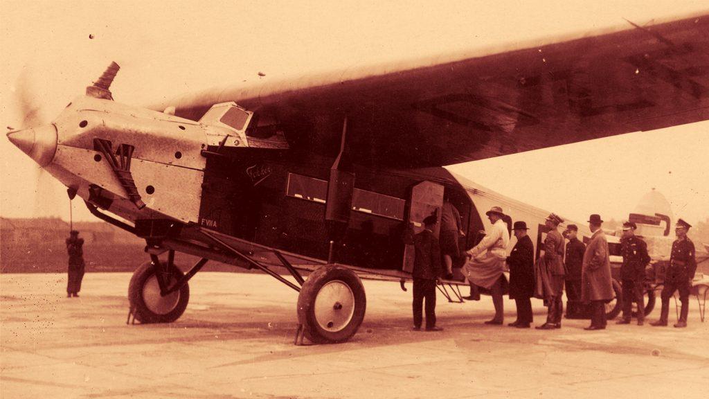 Pasażerowie wsiadają na pokład samolotu Fokker F VII A. Zdjęcie zamieszczone w taryfie lotów z 1930 roku