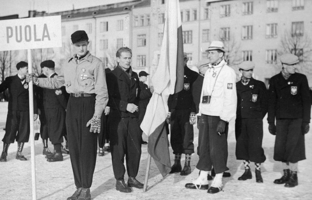 Polska ekipa podczas otwarcia mistrzostw świata w Lehti. Polską flagę trzyma Stanisław Marusarz (domena publiczna).