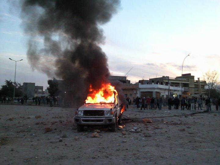 Protest przeciwko reżimowi Al-Kadafiego w Al-Bajda. Na pierwszym planie płonący policyjny samochód. Luty 2011 (domena publiczna).