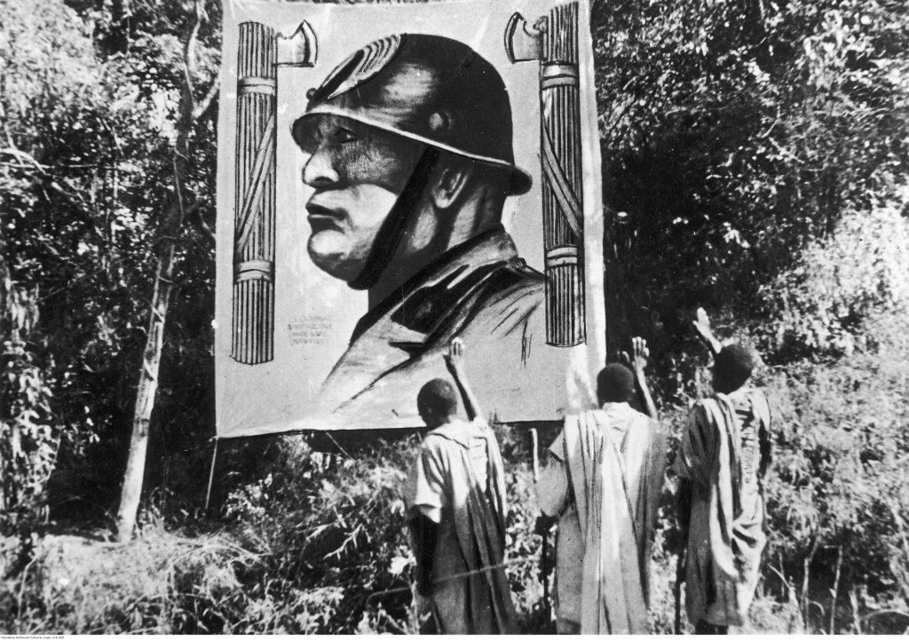 Mieszkańcy podbitej przez Włochów Abisynii pozdrawiają podobiznę Benito Mussoliniego. (domena publiczna).