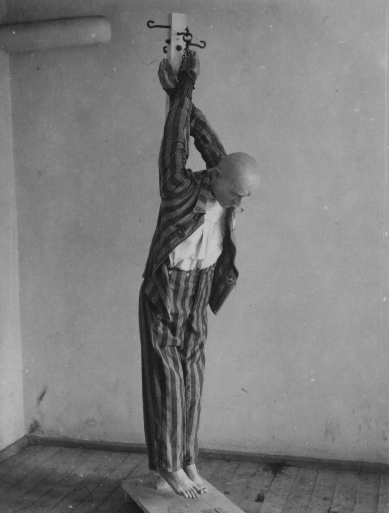 Kara słupka na pozowanym zdjęciu wykonanym przez amerykańskich żołnierzy niedługo po wyzwoleniu obozu w Dachau (domena publiczna).