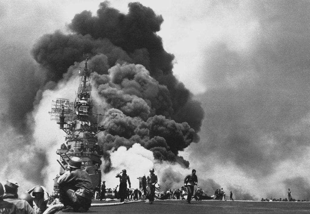 """Płonący lotniskowiec USS """"Bunker Hill"""" po tym jak został trafiony przez dwóch pilotów kamikaze (domena publiczna)."""