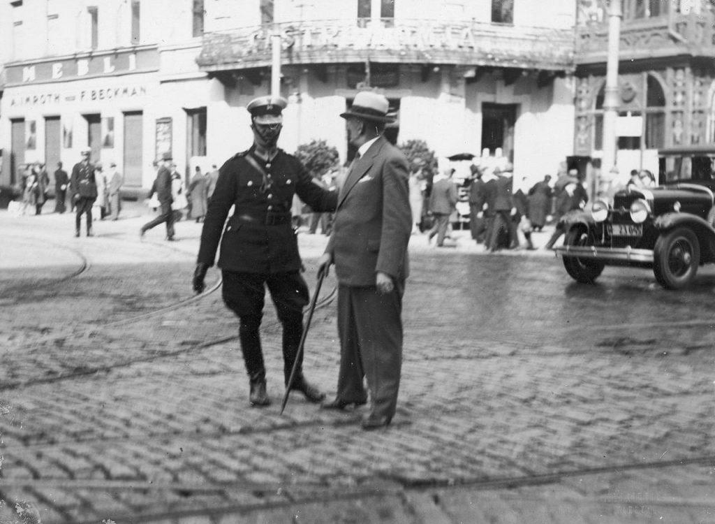 Warszawski policjant poucza pieszego, który źle przechodził przez jezdnię. A mógł dać mandat (domena publiczna).
