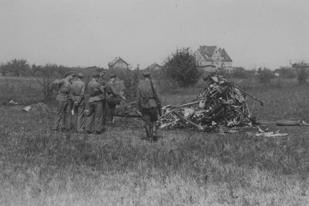 Grupa żołnierzy przy szczątkach samolotu, z 3 pułku lotniczego, który rozbił się w 1930 roku pod Poznaniem (domena publiczna).