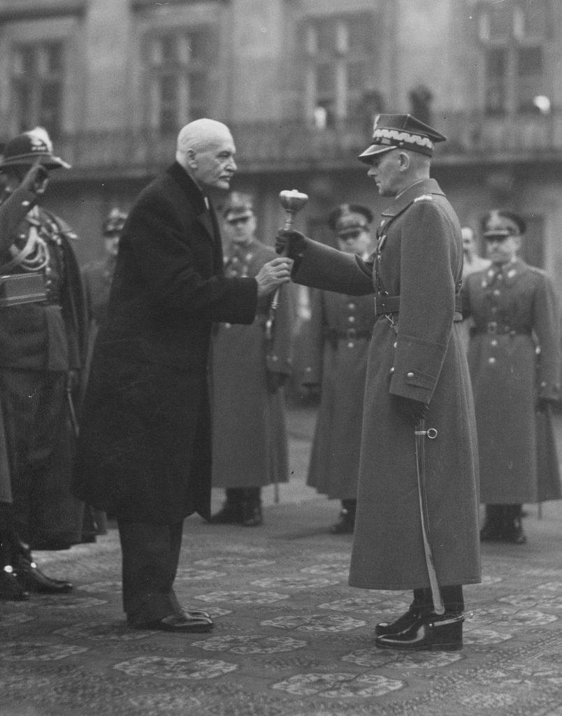 Dla Mościckiego i Rydza internowanie przez Rumunów było całkowitym zaskoczeniem dla sanacyjnych polityków. Na zdjęciu prezydent Mościcki wręcza buławę marszałkowską Śmigłemu (domena publiczna).