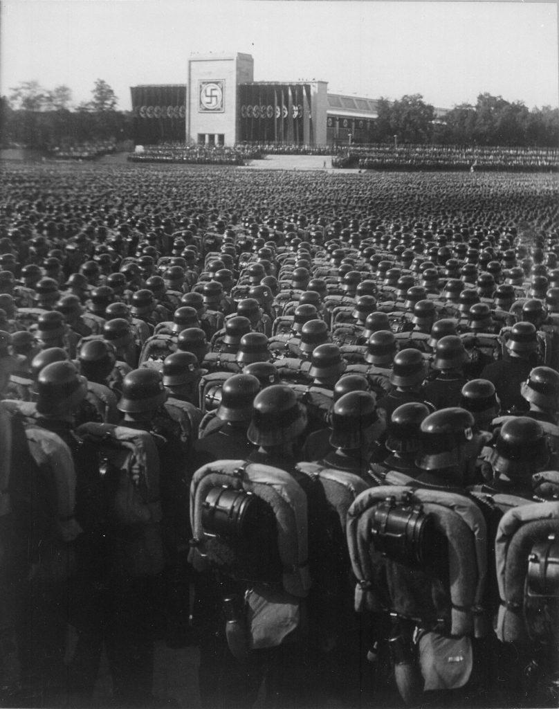 """Oddziały bojowe SS, SA i NSKK na zdjęciu z 1935 roku. W ich skład wchodził między innymi pułk """"Germania"""" (domena publiczna)."""