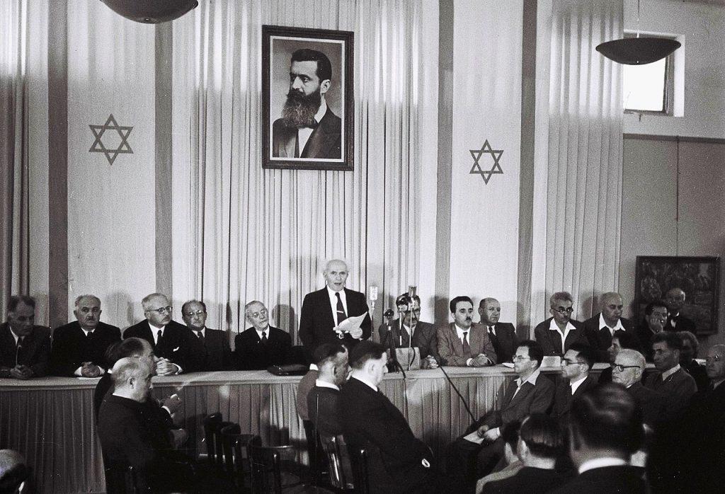 Dawid Ben Gurion (na zdjęciu już jako premier Izraela stoi z kartką) doskonale zdawał sobie sprawę z tego, że deklaracja ONZ wcale nie gwarantuje powstania Państwa Izrael. (domena publiczna).
