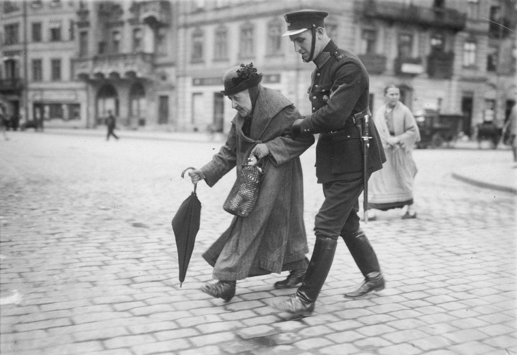 W pierwszych latach niepodległości, aby zwerbować więcej policjantów ogłaszano nabór na łamach gazet. Na zjęciu z 1925 roku warszawski mundurowy pomaga staruszce (domena publiczna).