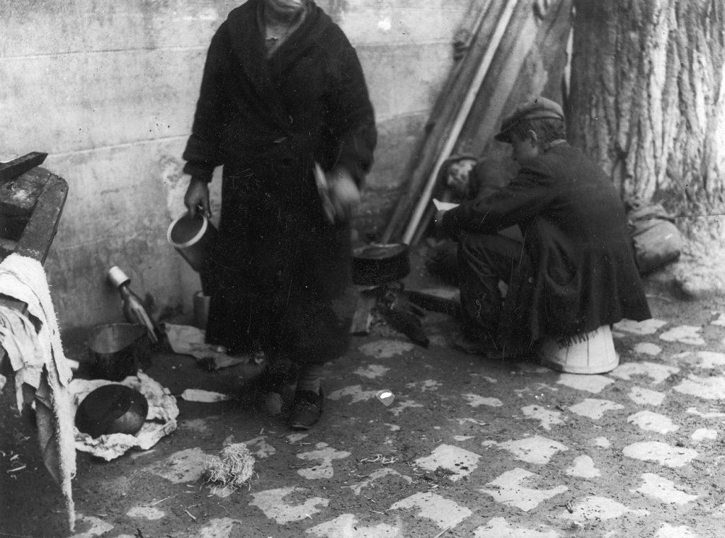 Żebracy na ulicy niezidentyfikowanego miasta. Lata 30. XX wieku (domena publiczna).