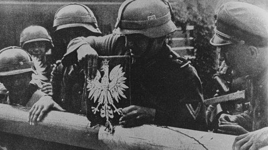 Niemieccy żołnierze zrywają polskie godło ze szlabanu granicznego