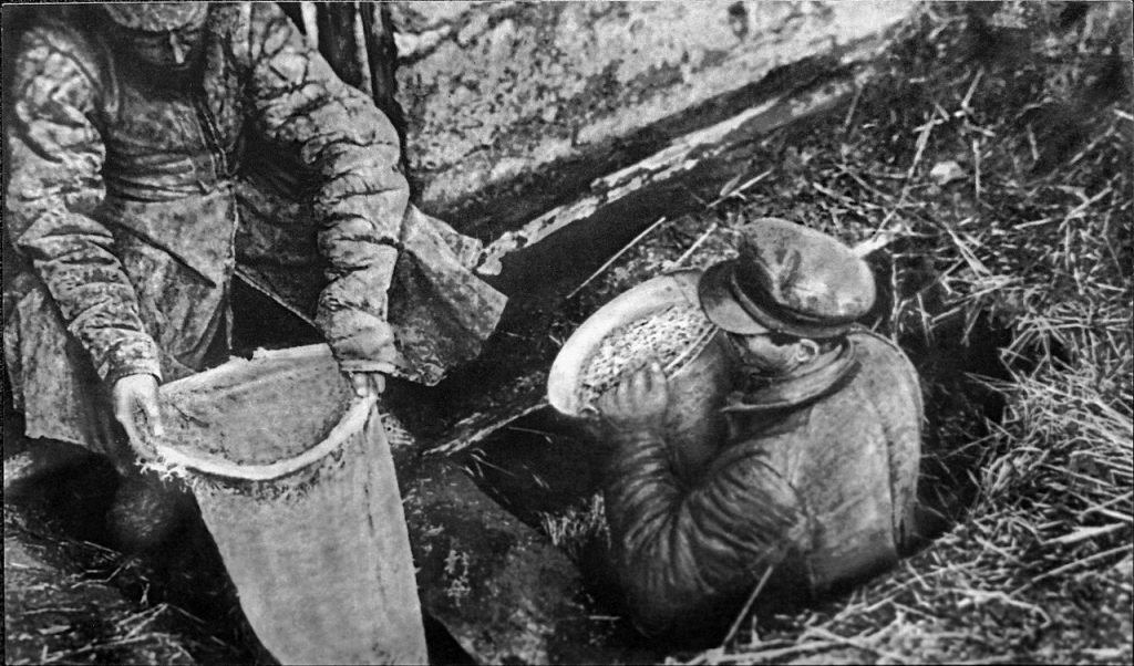 Funkcjonariusze  OGPU w trakcie konfiskowania resztek chłopskiego zboża (domena publiczna).