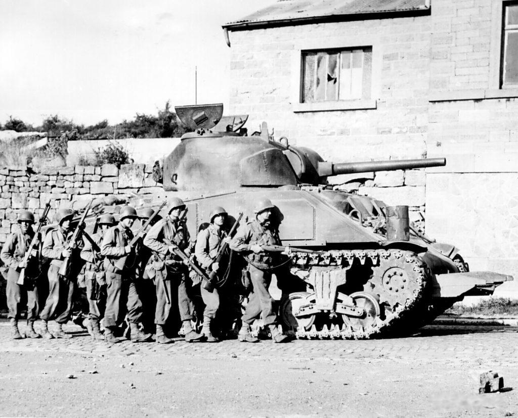 Amerykańscy żołnierze piechoty chroniący się za shermanem. Zdjęcie poglądowe z września 1944 roku (domena publiczna).