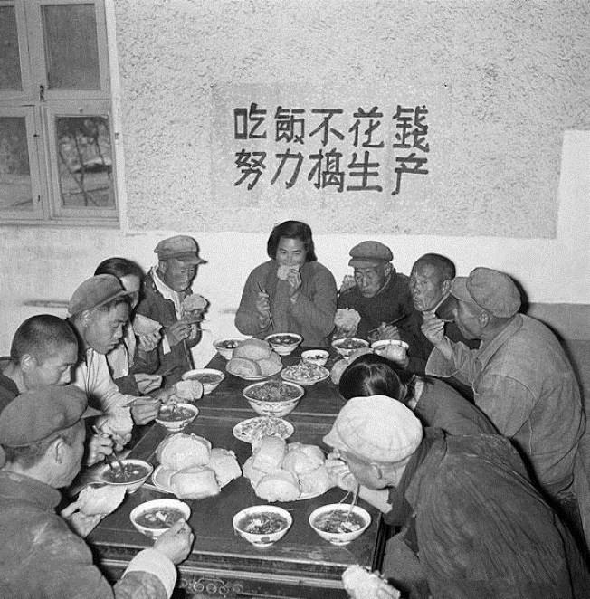 """Propagandowe zdjęcie z 1958 roku przedstawiające robotników podczas posiłku w stołówce. W tle plakat z napisem """"Jedz za darmo. Pracuj ciężko"""" (domena publiczna)."""
