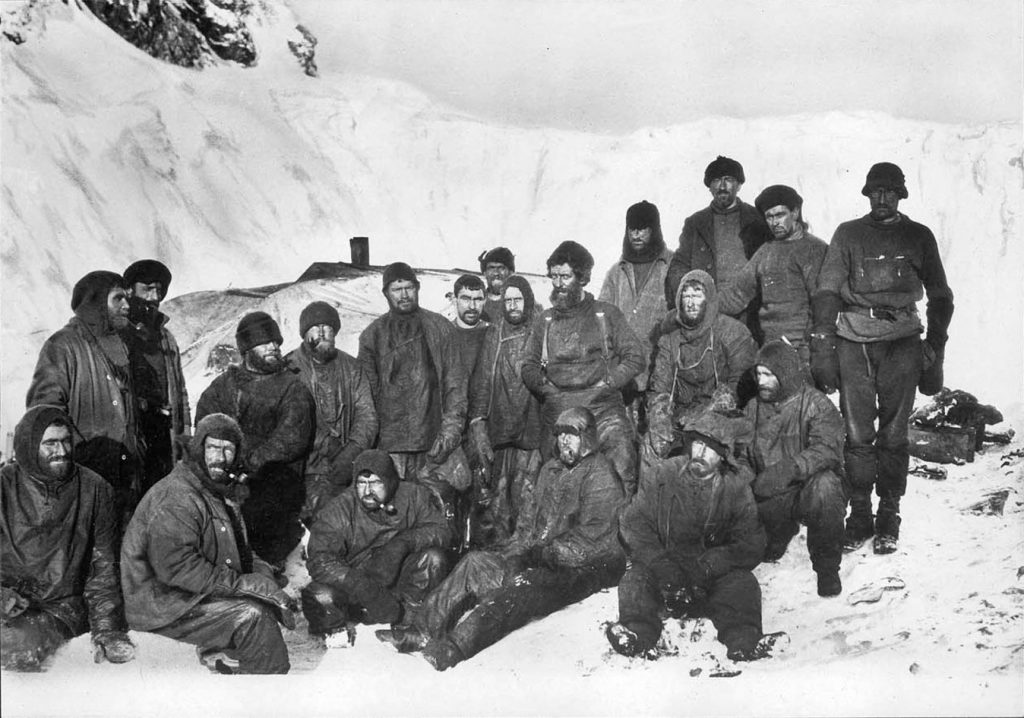 Załoga Shackletona na Wyspie Słoniowej. Bakewell klęczy trzeci od prawej (Frank Hurley/domena publiczna).