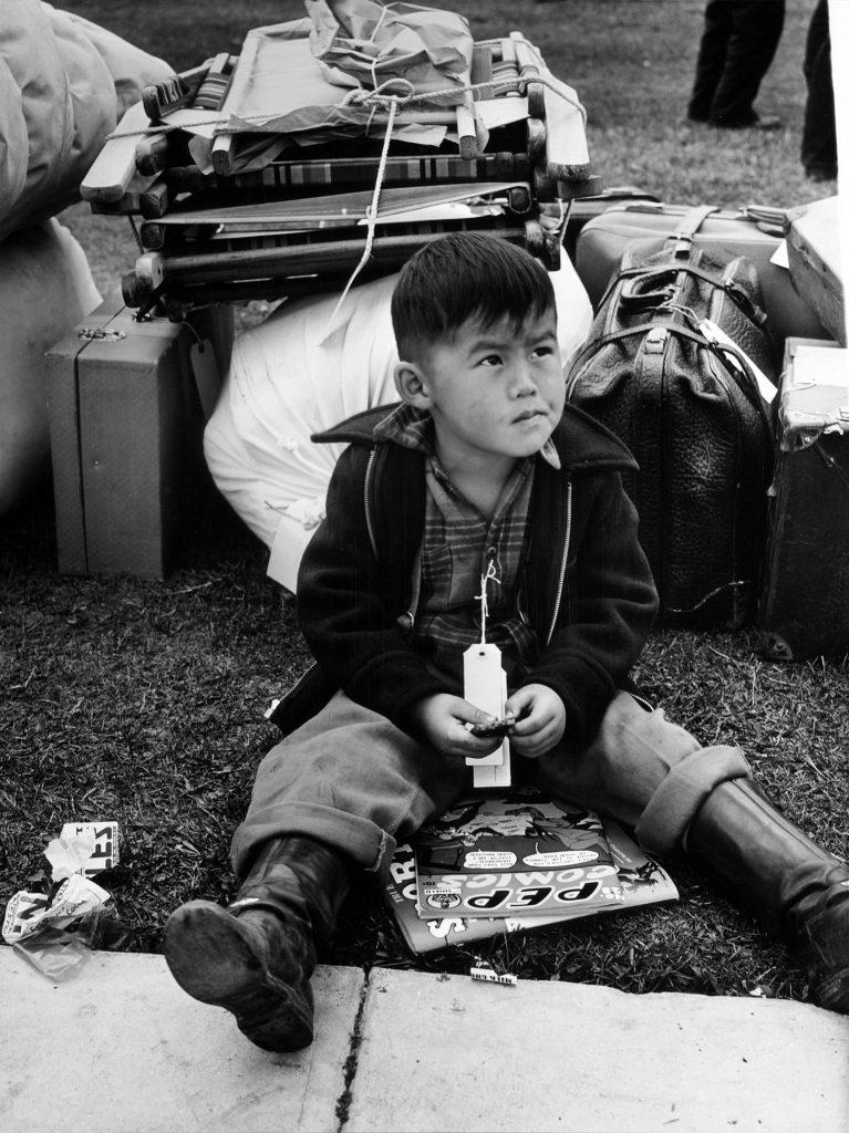 Chłopiec z numerem na szyi czeka na wywiezienie do jednego z obozów (Russell Lee/domena publiczna).