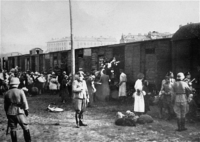 Niemcy ładujący kolejne ofiary na Umschlagplatz do pociągów jadących do Treblinki (domena publiczna).