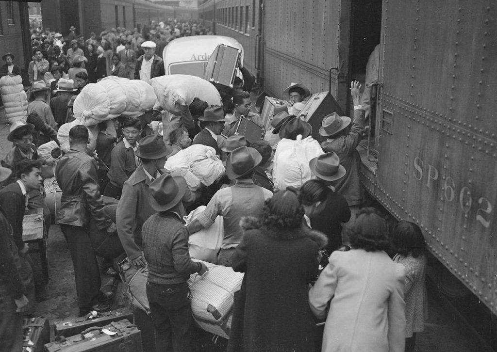 Zdjęcie (najprawdopodobniej z 1942 roku) przedstawiające mieszkańców Los Angeles o japońskich korzeniach opuszczających miasto (domena publiczna).