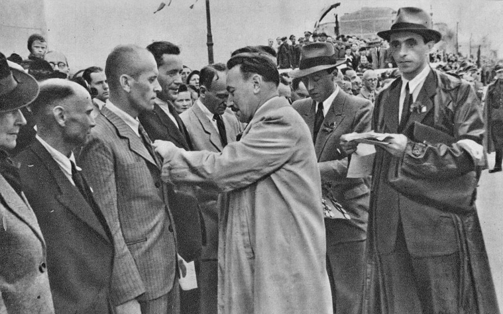 Ochroniarzom komunistycznych dygnitarzy zaraz po wojnie daleko było do profesjonalistów. Na zdjęciu Bolesław Bierut dekoruje robotników biorących udział w odbudowie Mostu Poniatowskiego (domena publiczna).