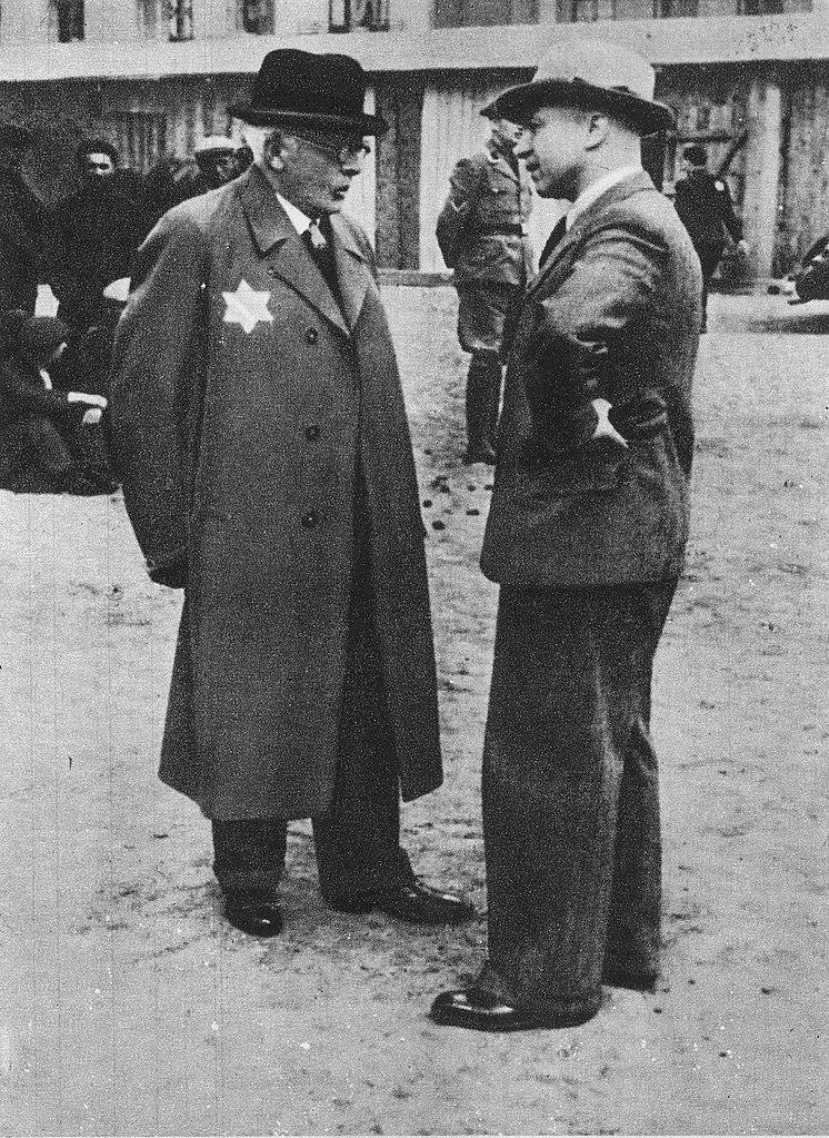 Chaim Rumkowski rozmawia z szefem niemieckiej cywilnej administracji Litzmannstadt Ghetto Hansem Biebowem (domena publiczna).