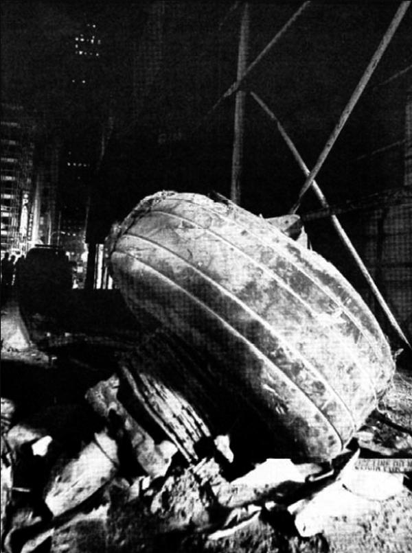 Element podwozia samolotu, który uderzył w północną wieżę WTC. Po przebiciu się przez budynek wylądował on kilkaset metrów dalej (domena publiczna).