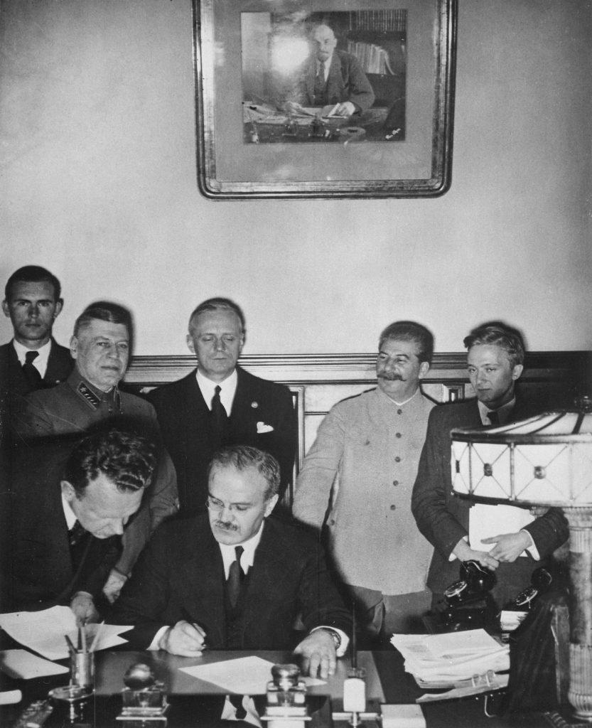 Mołotow podpisujący Traktat o granicach i przyjaźni III Rzesza – ZSRS. Z tyłu widoczni Stalin i von Ribbentrop (domena publiczna).