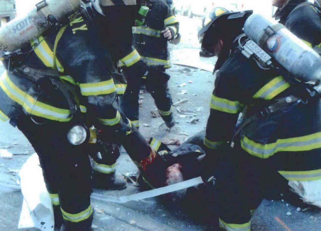 Ranny strażak na którego spadł odłamek z walących się wież WTC (domena publiczna).